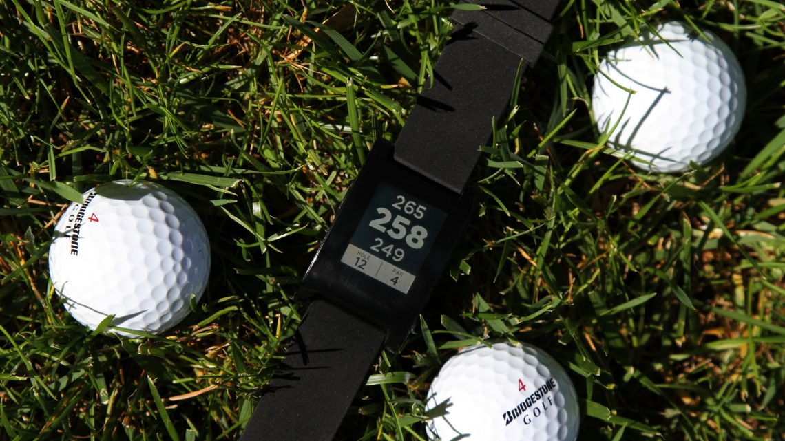pebble smart watch in grass with golf balls